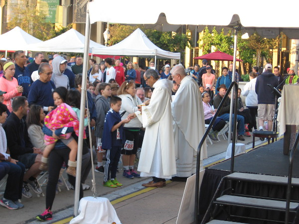 Catholic priests perform a religious service in the Plaza de Panama for the faithful before the Thanksgiving race to help the homeless.