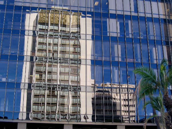 The Westgate Hotel building rises in the windows of 225 Broadway in San Diego, the former NBC building.