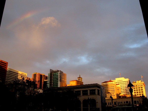 The sun breaks through storm clouds and shines upon downtown San Diego. A faint rainbow appears above.
