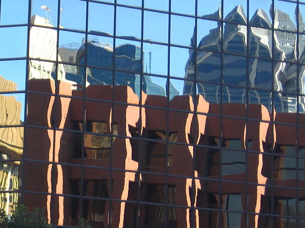 Unusual geometry caused by multiple reflections seen from street level.