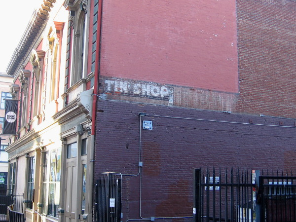 Old tin shop sign still visible on the historic I.O.O.F. building in San Diego's Gaslamp Quarter. A remnant of a past era.