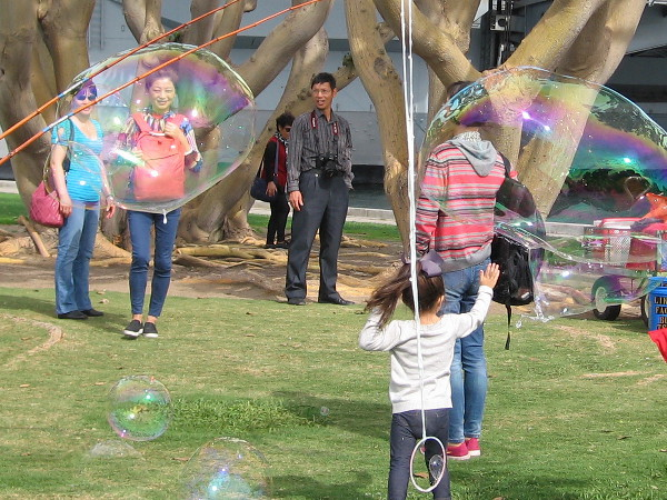 Tourists on San Diego's Embarcadero have fun with gigantic bubbles.