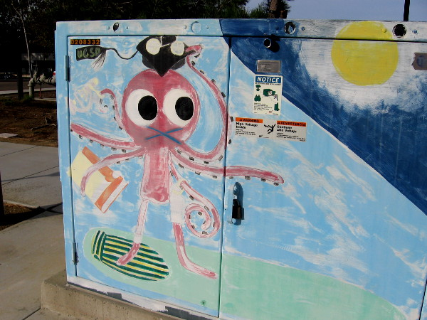 Across from the North Campus of UCSD, this octopus carrying a book and donning a graduation cap is riding a surfboard!