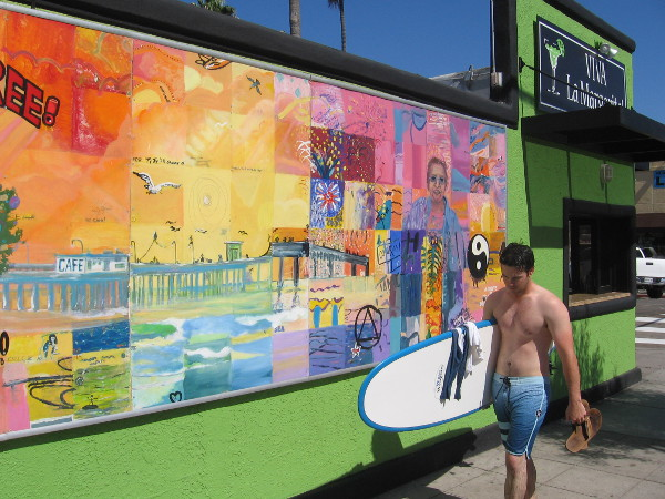 Surfer walks past a community mural in Ocean Beach. The mural project was begun by OB artist Rich James in 1999. Residents each paint a square in the finished artwork.