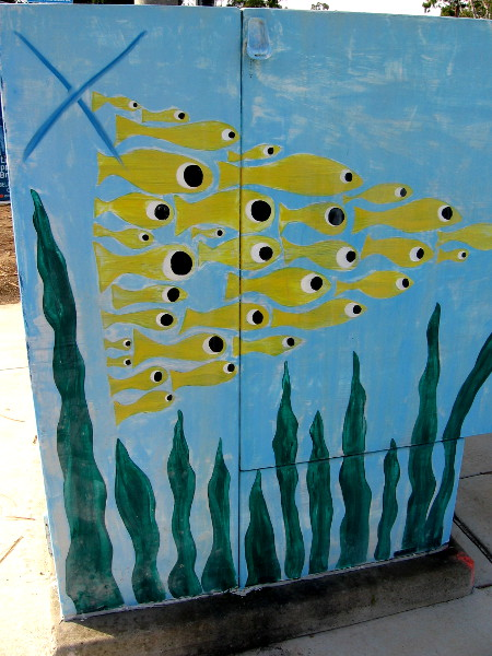 Another side of the big utility box has yellow fish forming a triangle as they swim above seaweed.