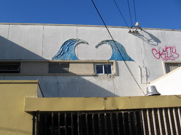 Images of breaking surf high on a building wall.