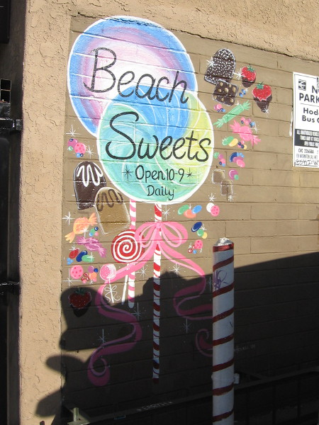 Candy and goodies depicted on a colorfully painted Beach Sweets sign.