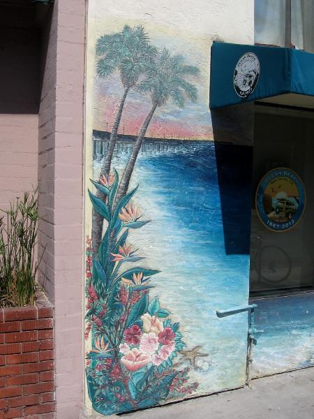 Art along a sidewalk shows lush vegetation and the OB pier.
