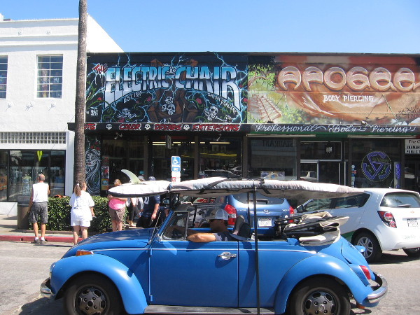 Car with surfboard drives down Newport Avenue past tattoo parlor street art signs.