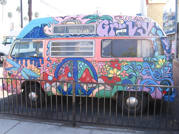 Volkswagen bug appears to have emerged from the 60s, with peace signs and psychedelic designs.