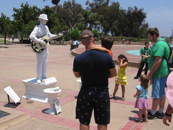 Families thrill to statue-like street musician in Balboa Park.