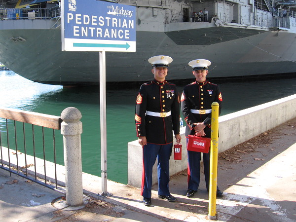 Marines stand at pedestrian entrance to Navy Pier, welcoming people to the Toys For Tots event by the USS Midway Museum.