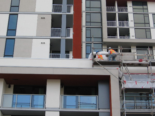 Construction workers put the finishing touches on a new downtown building.