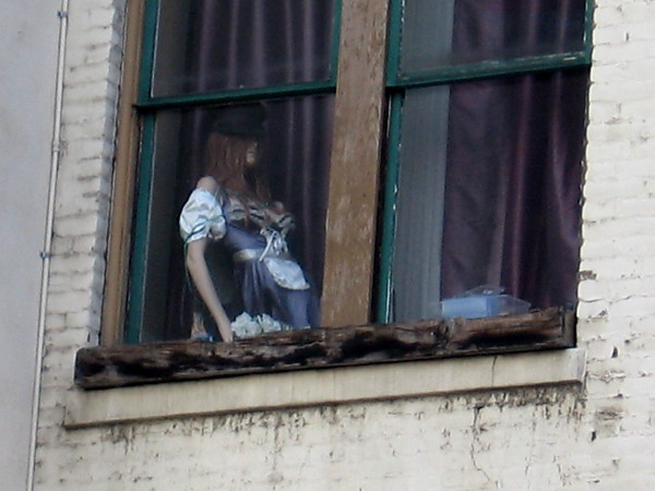 A mannequin high in a window makes one do a double take as one walks down Sixth Avenue through San Diego's Gaslamp.