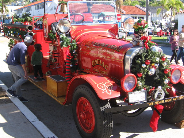 A kid checks out the bright red OMBAC Fire Department engine, which is seen in many San Diego area parades.