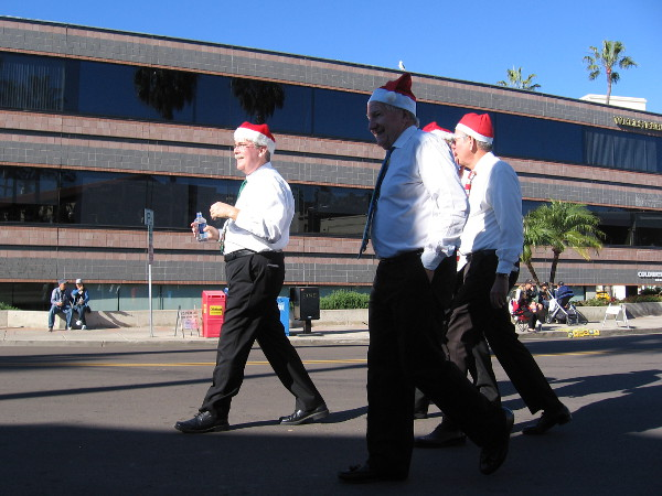 While people gathered along the parade route, these four guys in Santa hats came strolling along. They were singers!