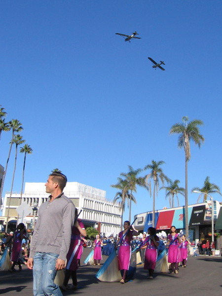 Biplanes continue to pass overhead as enthusiastic parade groups march and dance on by.