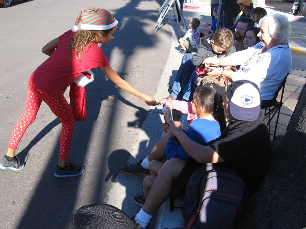 A young elf hands out Christmas candies to people watching La Jolla's joyful holiday parade.