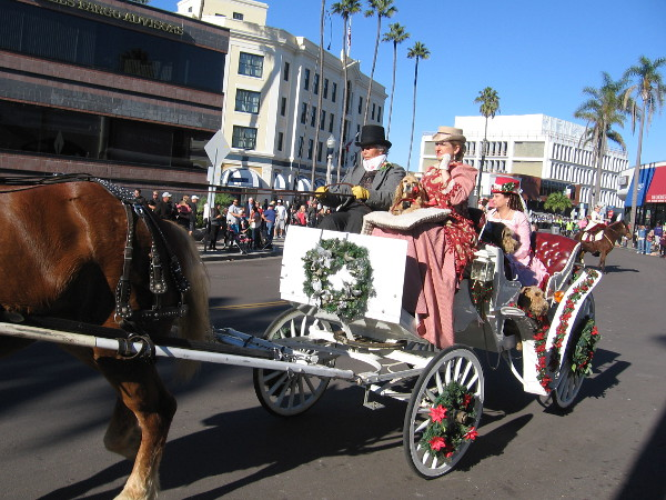 A horse and carriage and folks dressed in Victorian garb for Christmas.