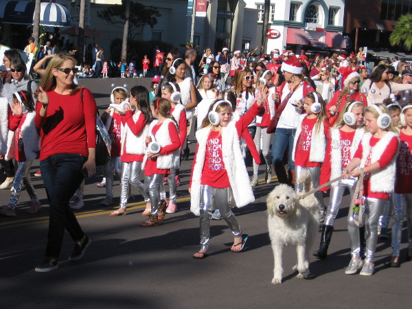 Here comes a Girl Scout Troop and a friendly dog.