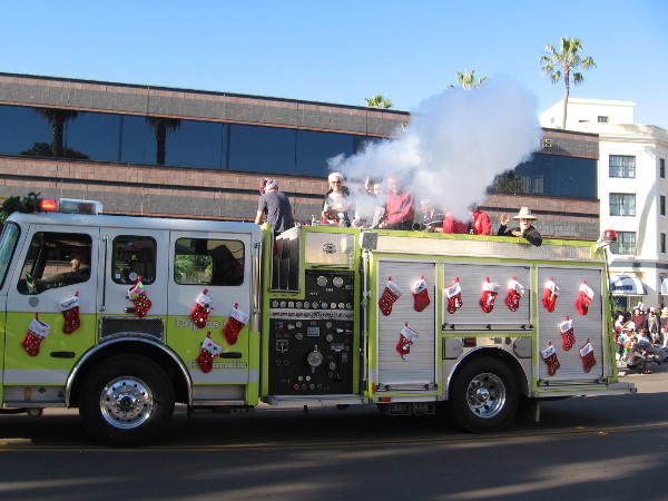 The La Jolla Sunrise Rotary Club was spraying Christmas snow onto the onlookers with their stocking covered fire truck!