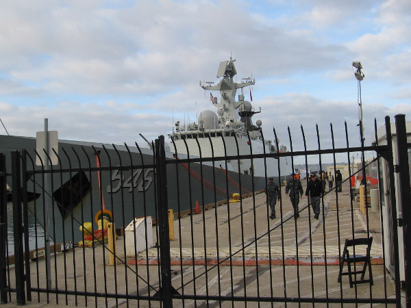 United States military personnel walk along the B Street Pier during a visit of the Chinese Navy to San Diego.