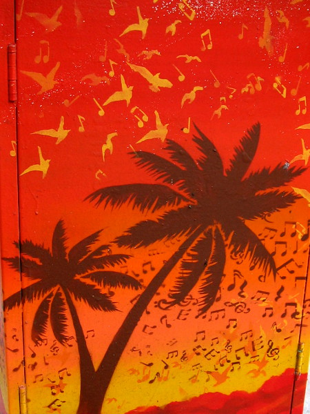Musical notes and birds fly among tropical palm trees. An image on a utility box warms the city as winter nears.
