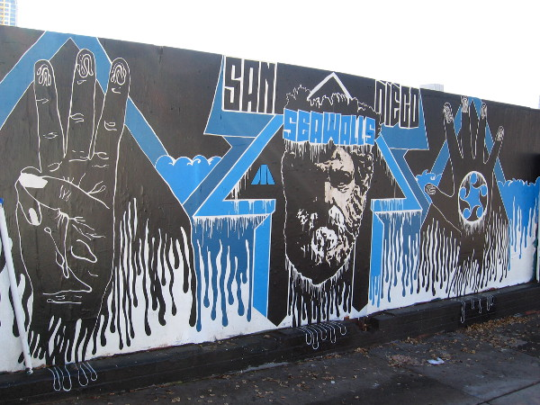 A San Diego Sea Walls mural on the same wall features a bearded face and two hands. Not sure about the symbolism.