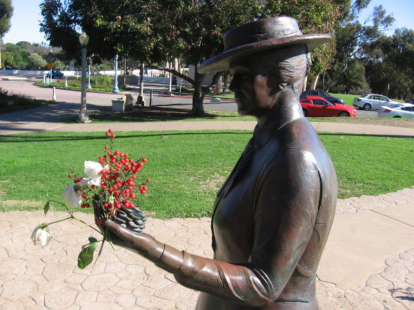 Bronze statue of Kate Sessions in Balboa Park's Sefton Plaza holds flowers. She planted many seeds a century ago.