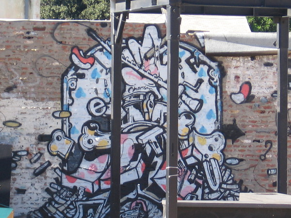 A very cool abstract jumble of street art on a brick wall.