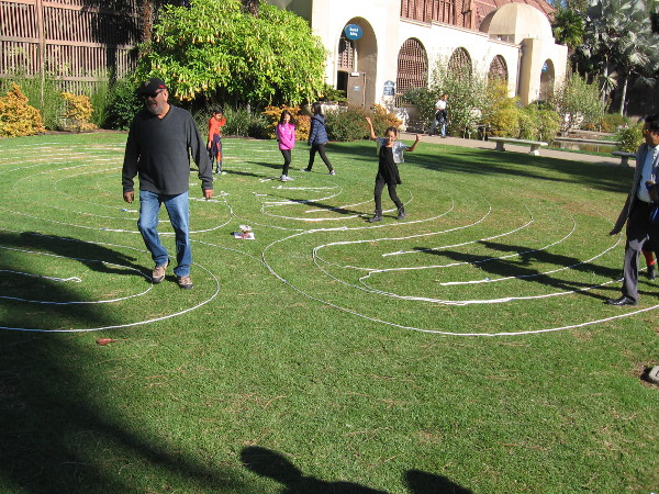 Visitors to Balboa Park walk the meandering single path of a labyrinth near the Botanical Building.