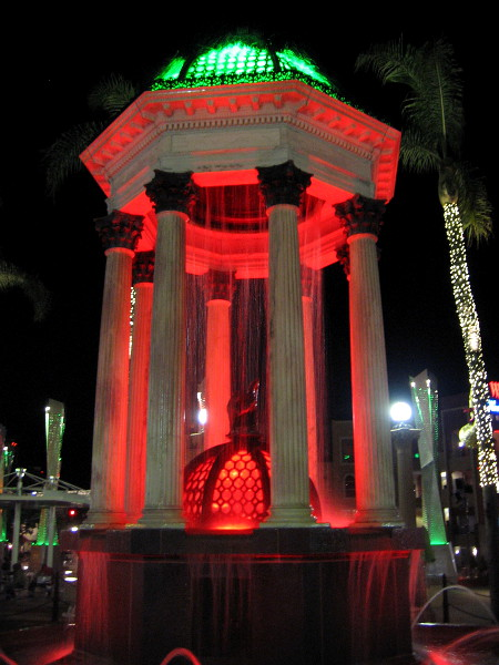 A closer photo of the handsome Broadway Fountain lit up at night with traditional Christmas colors.
