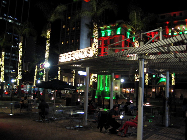 People sit at tables near the outdoor Starbucks at Horton Plaza Park one early mid-December evening.