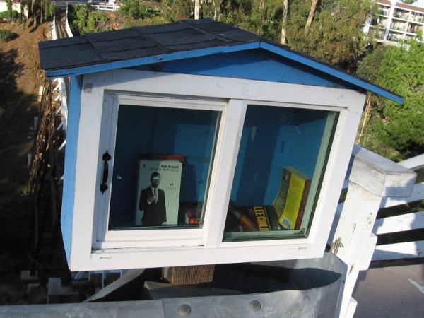 This fancy book box has a sliding glass door and sloped roof. You can find this tiny library at the east end of the Quince Street Trestle pedestrian bridge in Bankers Hill.