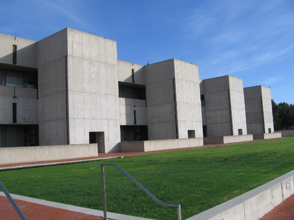 A monumental building made of smooth exposed concrete with simple, clean lines, between green grass and blue San Diego sky.
