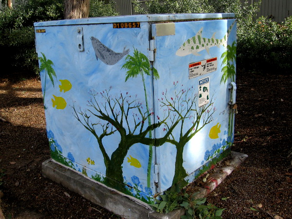A transformer box with fish and whales swimming among trees and flowers!