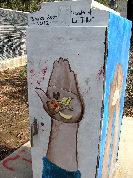 One side of a box near an entrance to UCSD. Hands of La Jolla by Rebecca Asch. It's holding food.