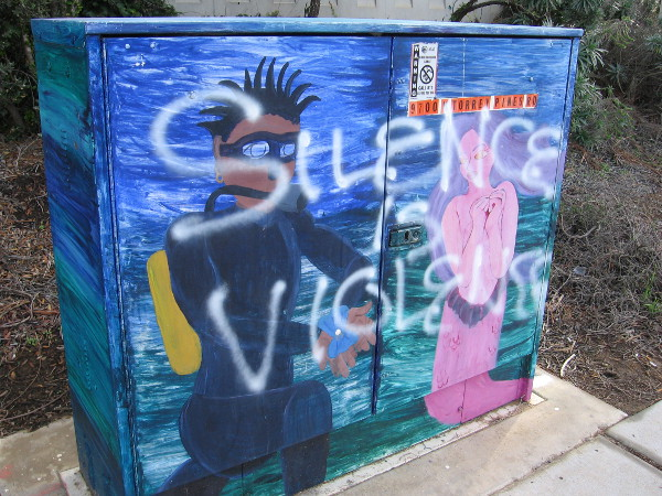 A guy in scuba gear seems to love a mermaid. The spray painted words Silence is Violence might have been applied later, or perhaps not.