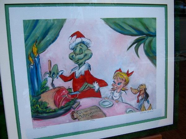 The Grinch is behaving unexpectedly unGrinchlike in this fun artwork inside the front window of The Chuck Jones Gallery.