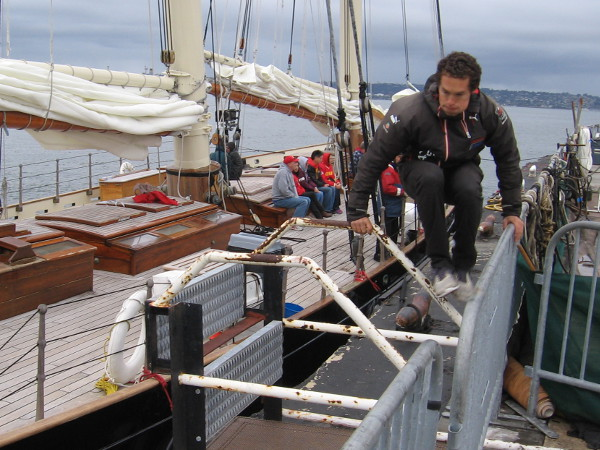 A member of America's crew leaps through the air to secure the beautiful ship, a replica of the racing schooner that ushered in The America's Cup.