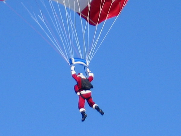 Old Saint Nick nimbly descends from the blue sky in order to greet the nice boys and girls of San Diego. Beats using a sooty chimney.