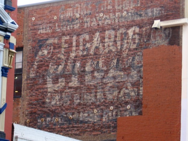 High up, painted on the old brick building's side is a fading advertisement. A glimpse of San Diego's past.