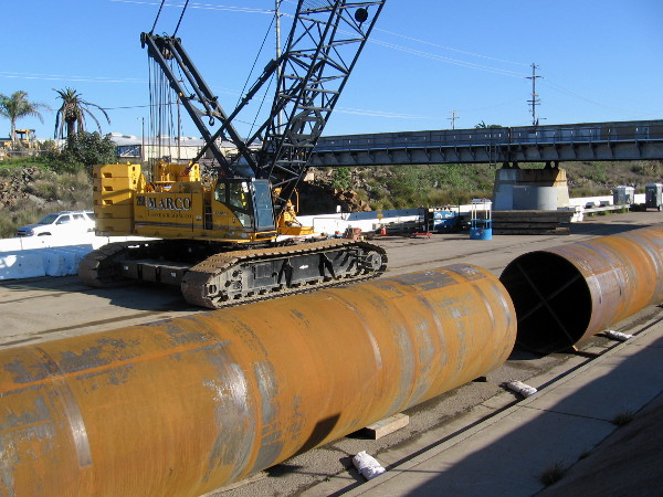 A crane and huge pipes are on Friars Road near the site of the San Diego River Double Track (SDRDT) project.