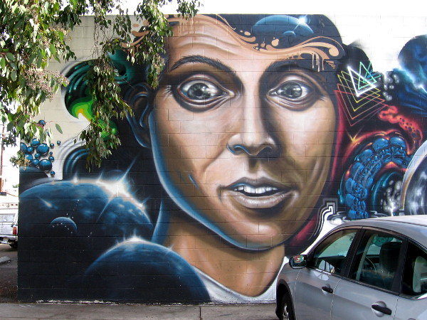 A wide-eyed human face on a wall in North Park, surrounded by cosmic imagery.