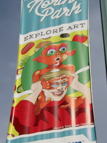 Street lamp banners along 30th Street in North Park feature imaginative faces. Explore Art.