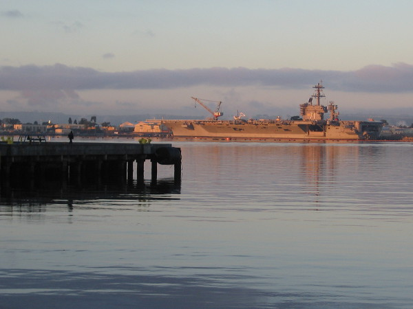 Early morning light turns aircraft carrier USS Theodore Roosevelt (CVN-71) golden. It is docked at Naval Air Station North Island.