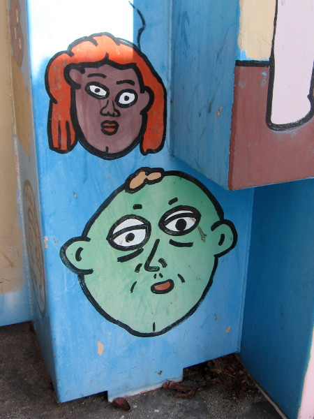 Funny graffiti faces on an electrical box.