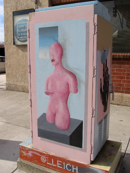 A bare pink face on a painted mannequin. Abstract street art in North Park.