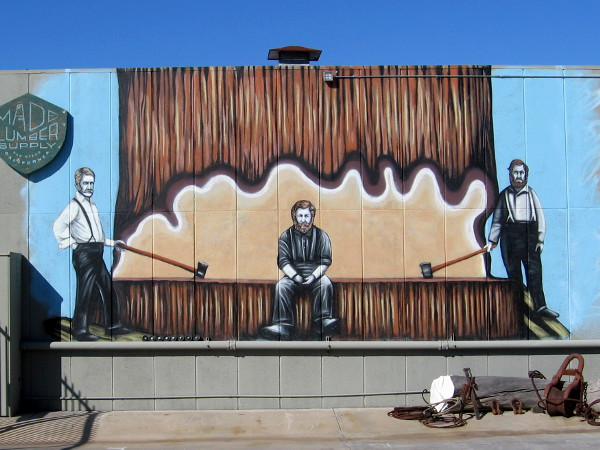Mural depicting three lumberjacks and one enormous tree on the wall of Made Lumber Supply in San Diego.