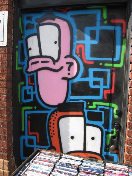 Two funky faces watch people walking down the sidewalk from a window above a bin of CD's.